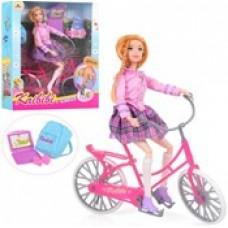 Кукла Кайлили на велосипеде.